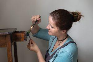 Photo d'une femme peignant un meuble